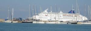 Nine Lives dwarfed by a cruise ship